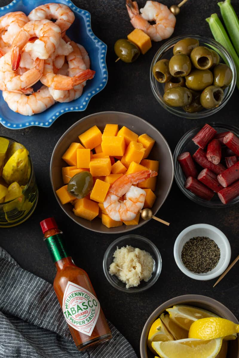 various small bowls with different garnishes including shrimp, olives, beef sticks, pickles, cheese cubes, horse radish, pepper, and Tabasco sauce