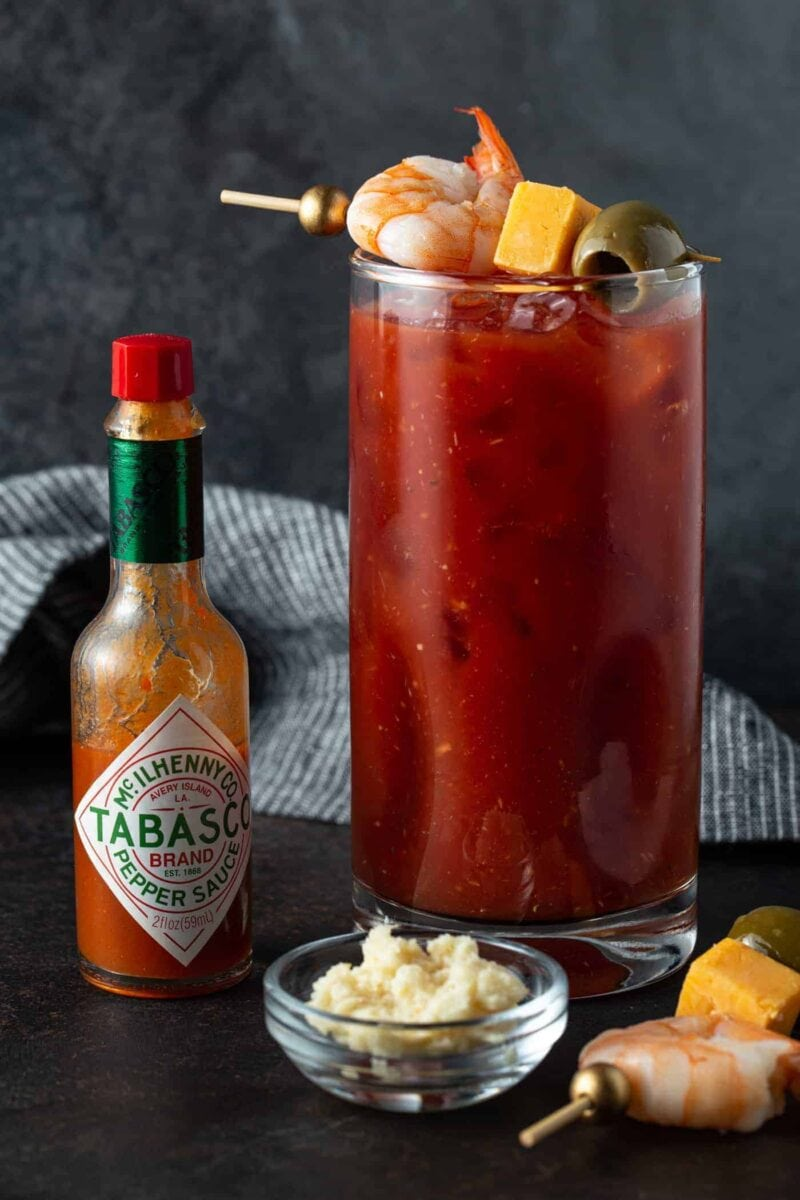 High Ball glass filled with Bloody Mary and garnished with skewer filled with shrimp, cheese and olive. Tabasco bottle and bowl of horseradish for garnish.