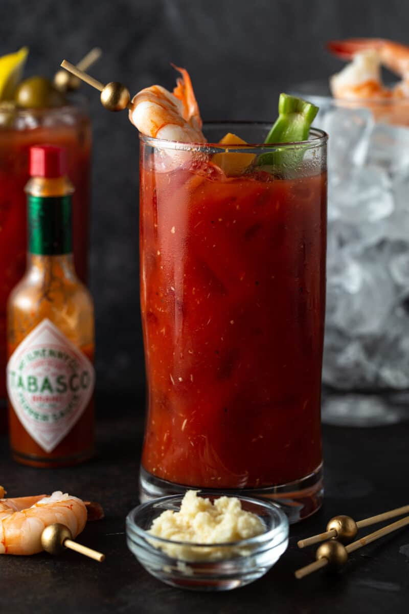 High Ball filled with Bloody Mary and garnished with skewer of olives and shrimp. Empty glass filled with ice in the background on a dark surface.