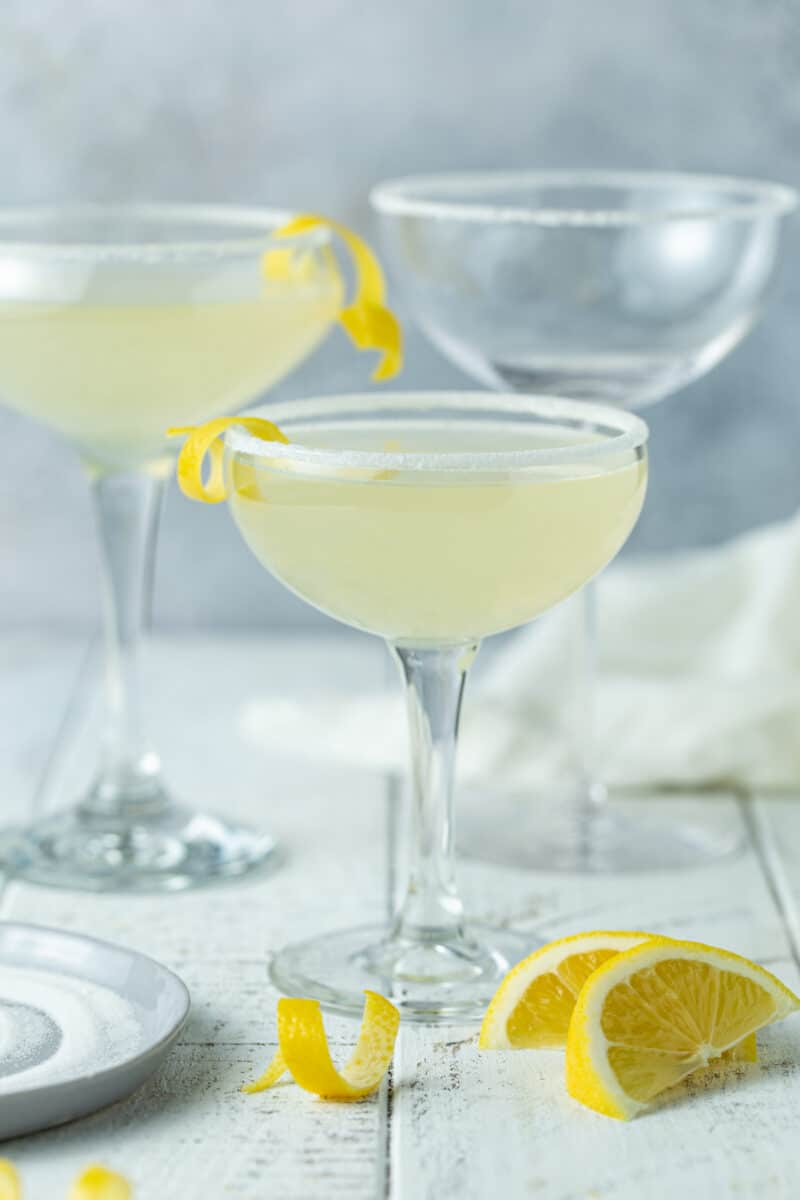 3 martini glasses on a gray background filled with lemon drop martniins and garnished with lemon twists.