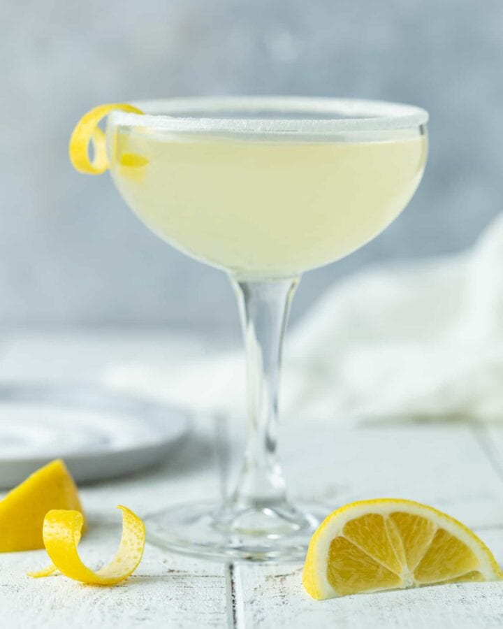 Single Elderflower Martini cocktail in a coupe glass with a lemon twist and a sugared rim on a white background.