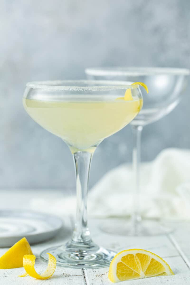 Single Lemon drop drink in a small coupe glass with a lemon twist.