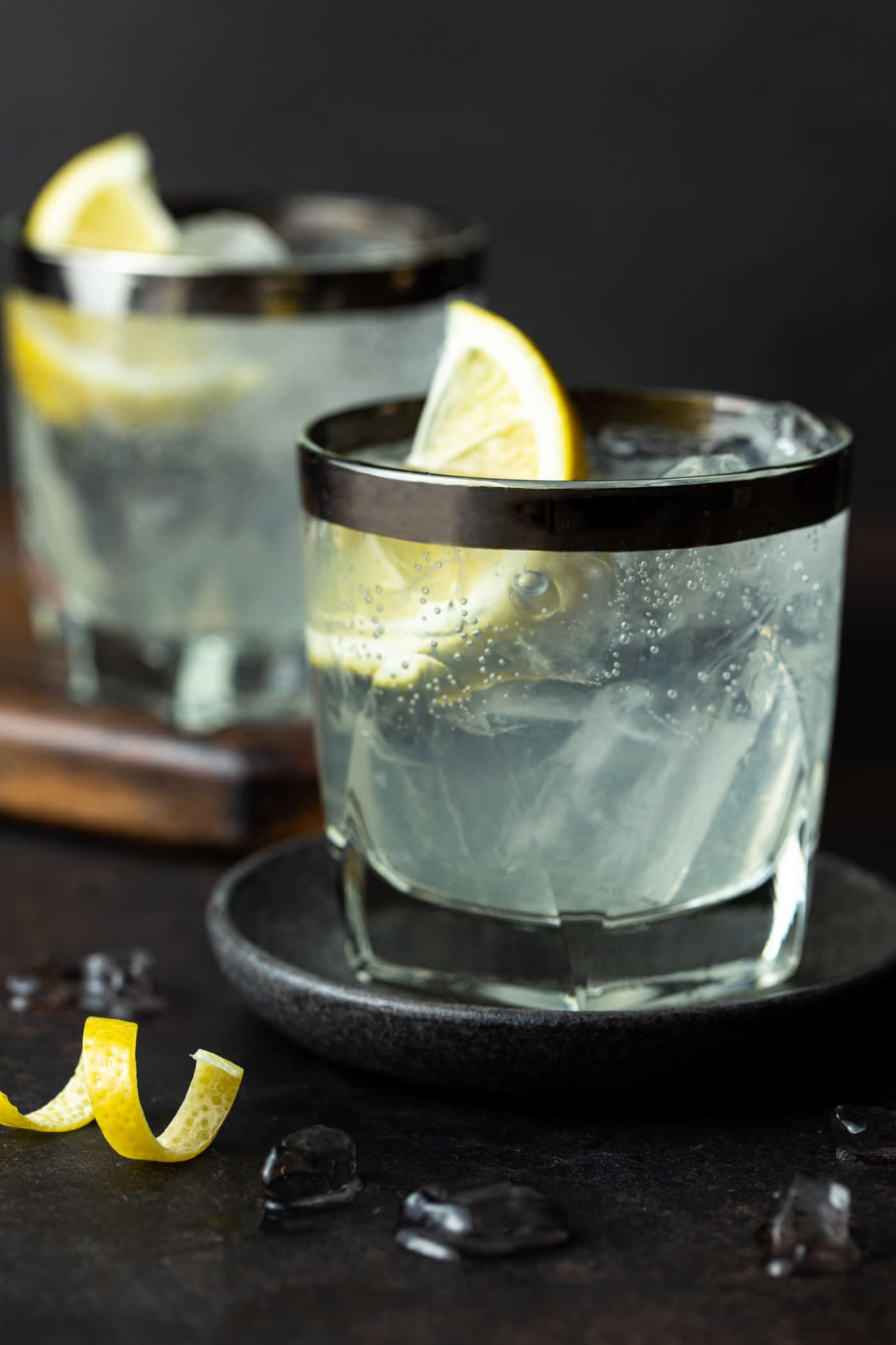 Two lowball glasses filled with Elderflower Vodka Sodas. Garnished with fresh lemon wedges and a lemon peel twist.