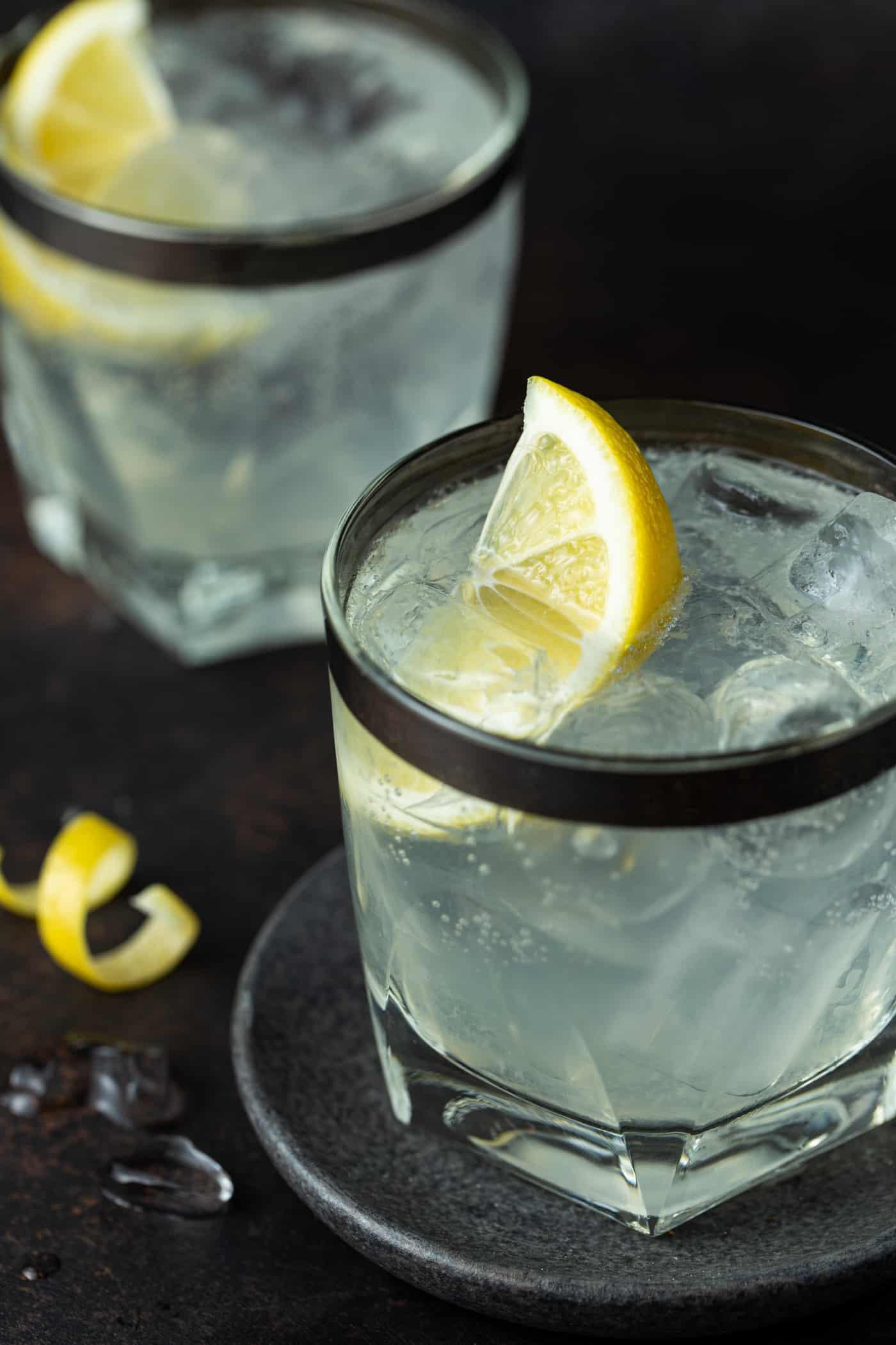 Two lowball glasses filled with Elderflower Vodka Soda. Garnished with fresh lemon wedges.