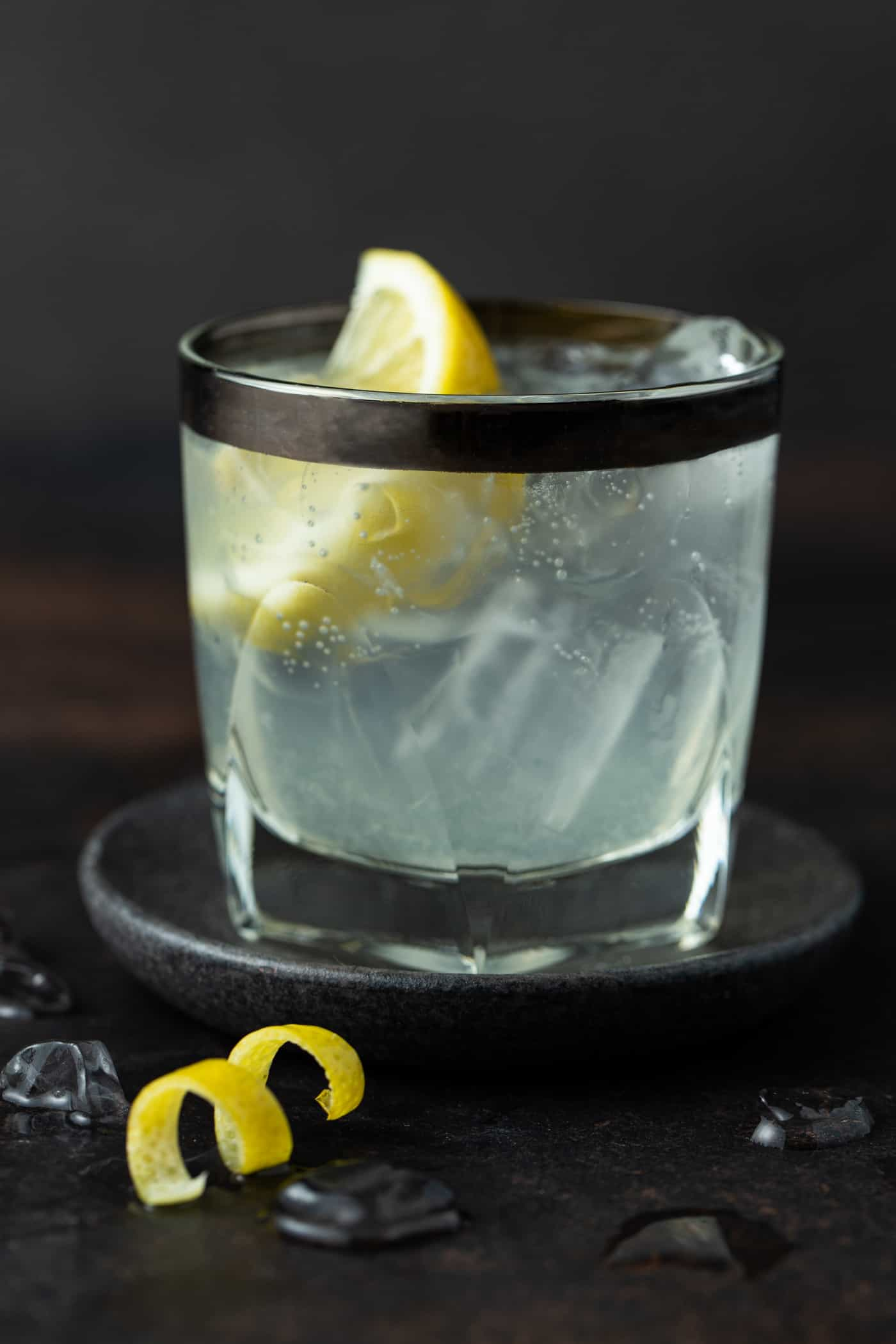Lowball glass with silver rim. Filled with Elderflower Vodka soda. Garnished with a fresh lemon wedge.