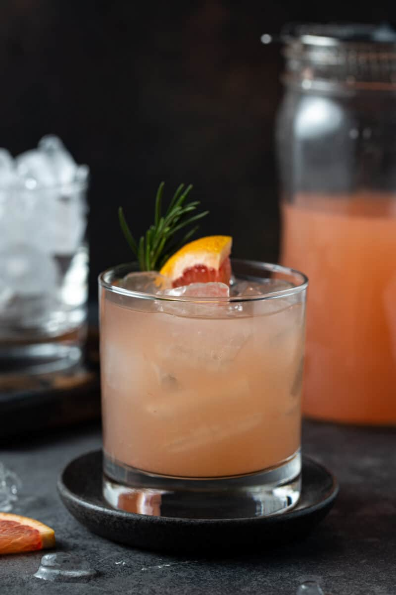 Low ball glass filled with ice, grapefruit juice, gin and garnished with fresh rosemary and a grapefruit wedge on a dark background