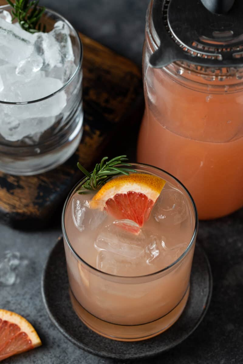 3/4 angle of low ball glass and shaker filled with grapefruit juice and gin on a dark grey coaster with a slate gray background.