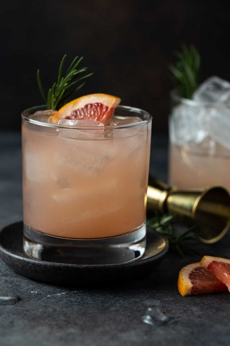 Greyhound drinks in low ball glasses on dark gray coasters with fresh grapefruit for a garnish.