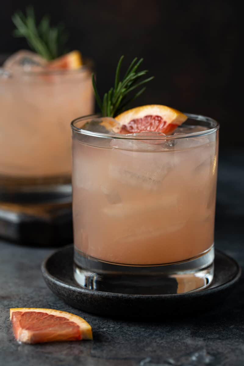 Greyhound cocktails in low ball glasses with lots of ice, fresh rosemary for a garnish along with a fresh grapefruit wedge.