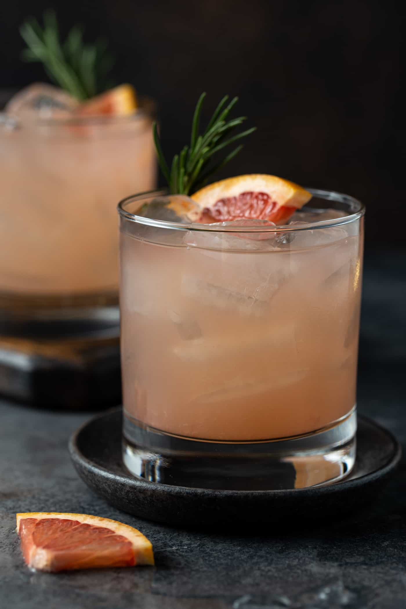 cocktails in low ball glasses with lots of ice, fresh rosemary for a garnish along with a fresh grapefruit wedge.