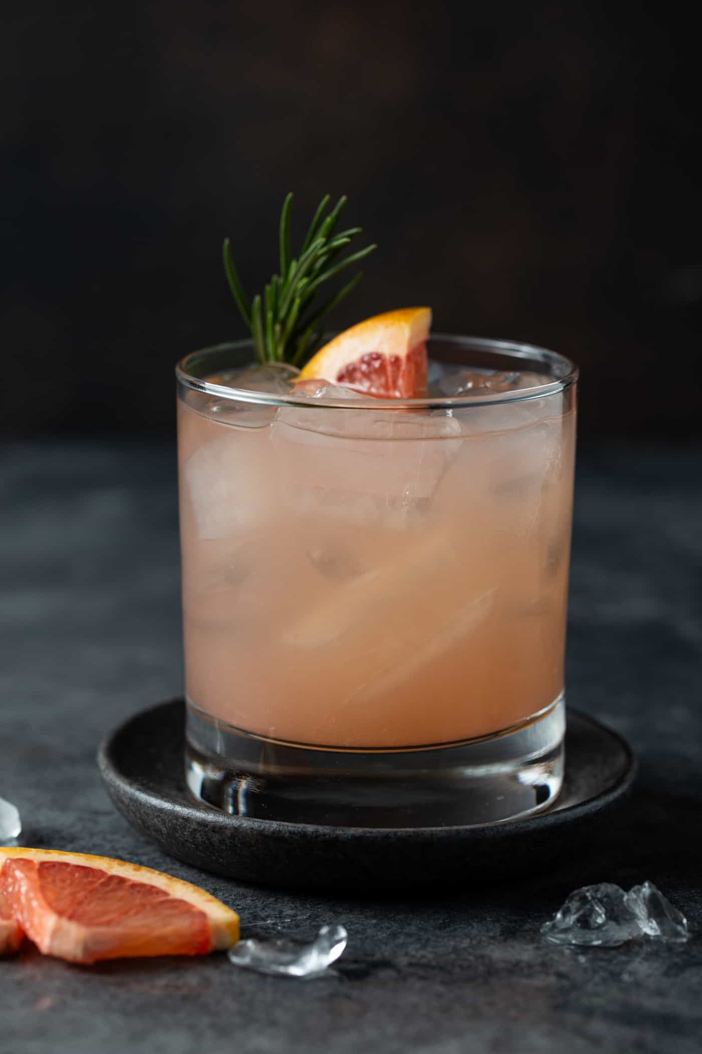 Close up image of pink grapefruit juice in a low ball glass on a dark background.