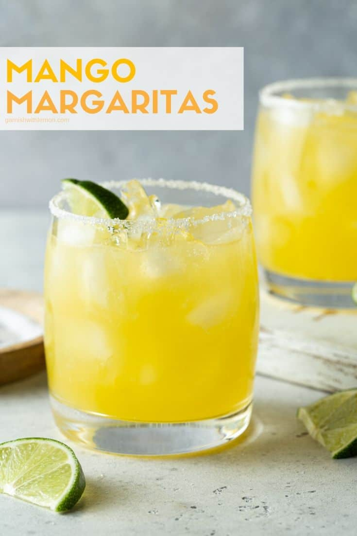 Two lowball glasses filled with mango margarita, rimmed with salt and garnished with lime wedges.