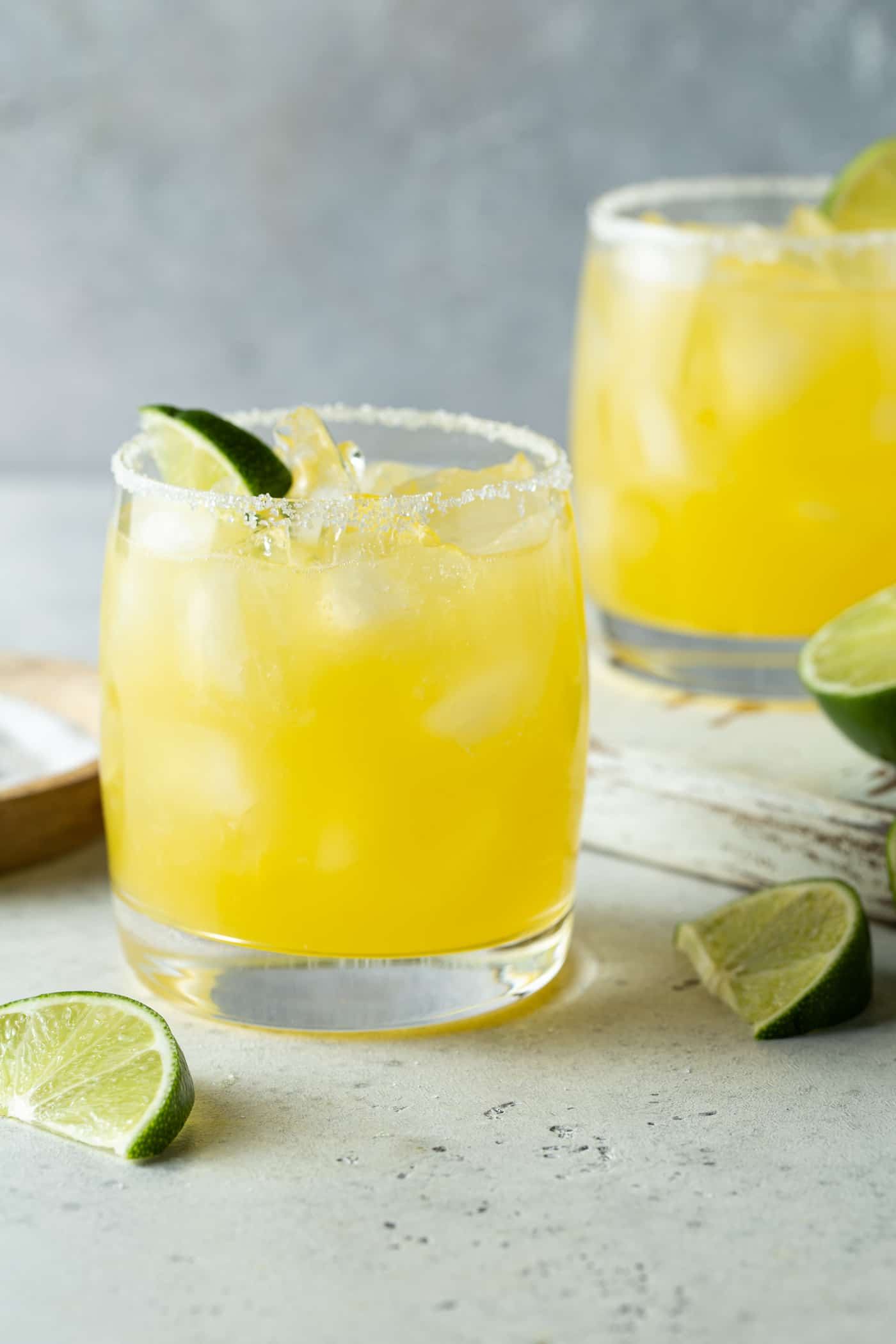 Two lowball glasses of mango margarita. Garnished with fresh lime wedges.