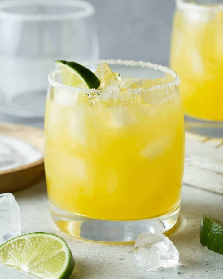 Lowball glass filled with mango margarita and garnished with a fresh lime wedge.