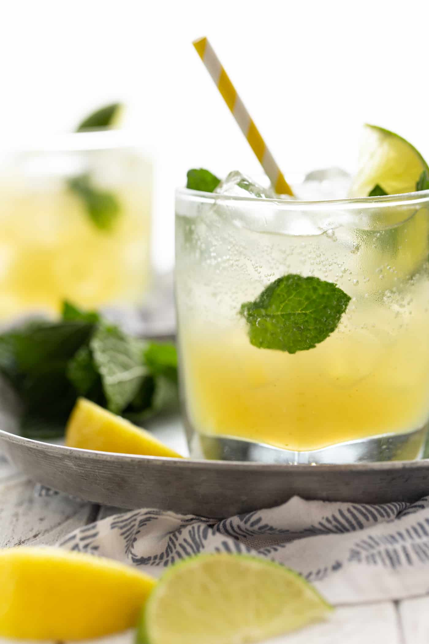 Cocktails in low ball glasses with fresh mint leaves and lemon wedges for garnish.