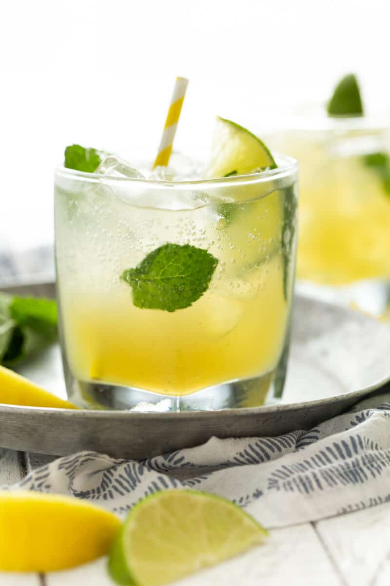 low ball glass filled with ice and mint leaves and bootleg cocktails. On a silver tray with a yellow straw.