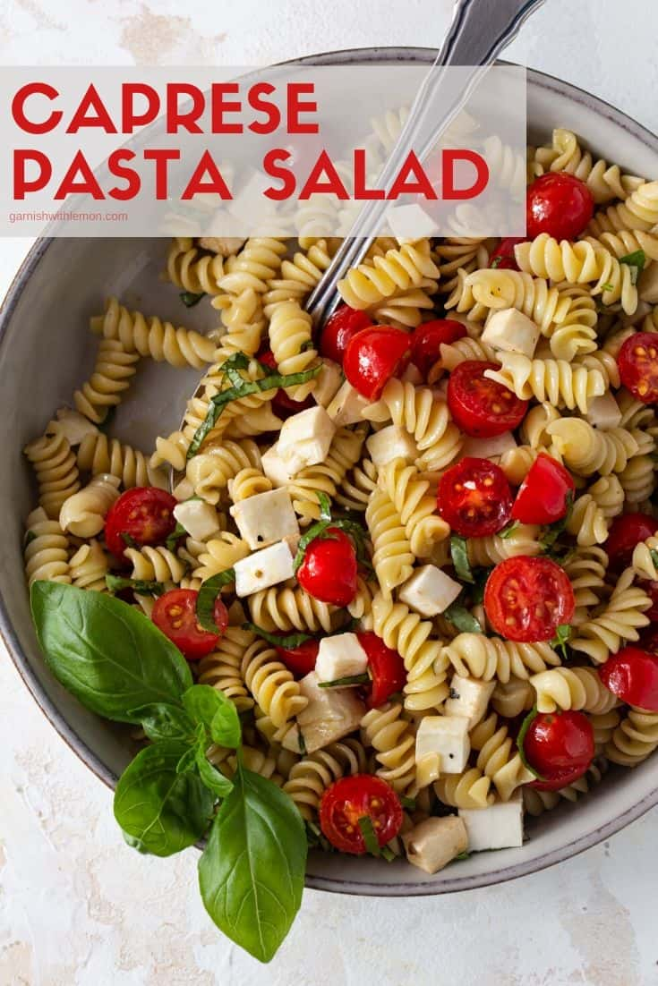 Pinterest image of Caprese Pasta Salad in a gray bowl with fresh basil leaves for garnish.