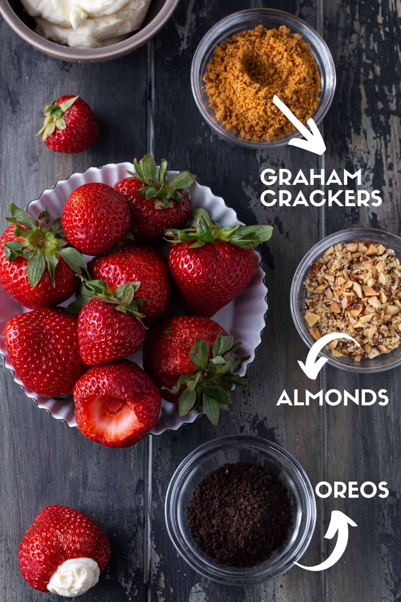 Small bowls of crushed Oreos, graham crackers and almonds next to strawberries and cheesecake filling.