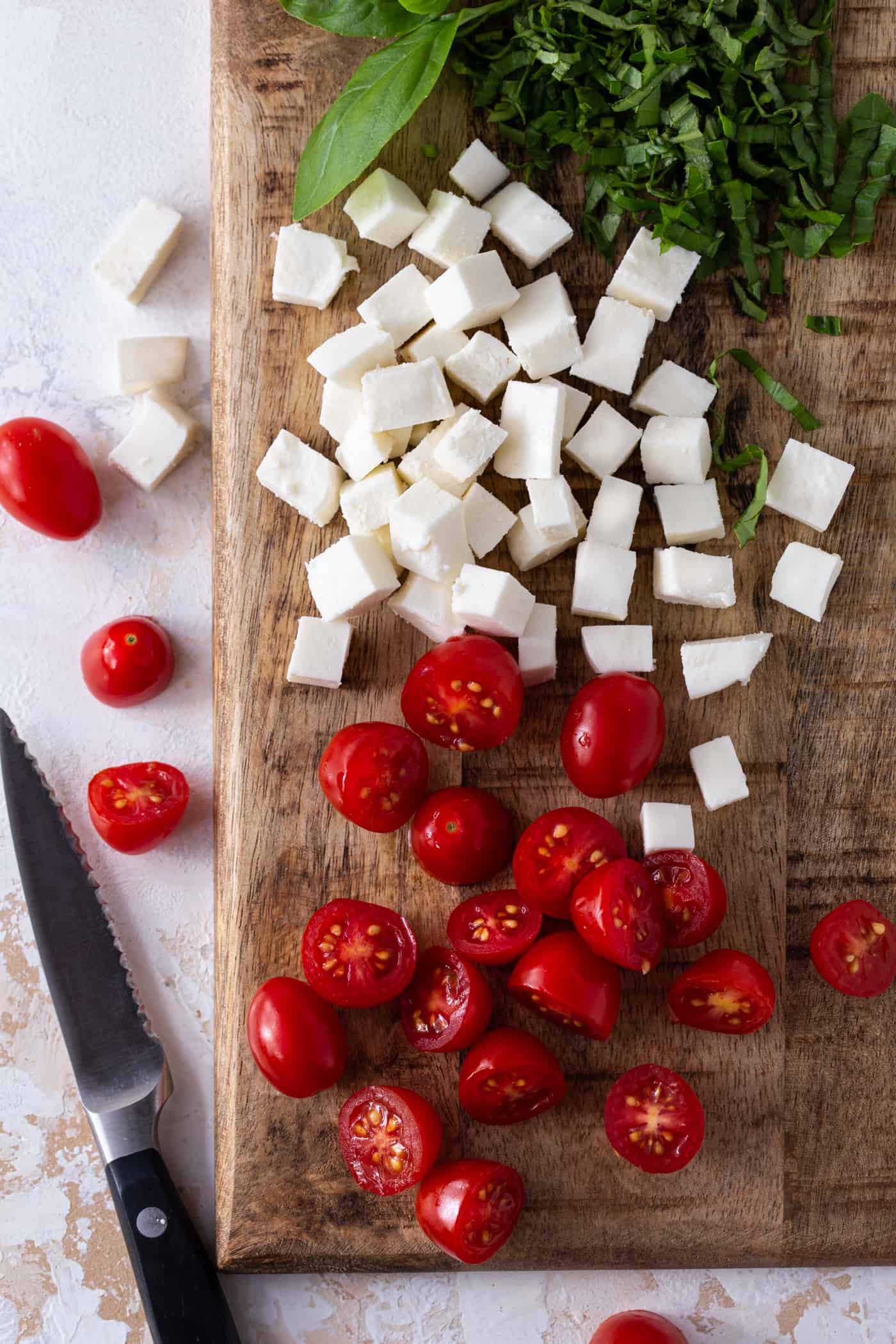 Fresh mozzarella, cherry tomatoes and fresh basil on cutting board.