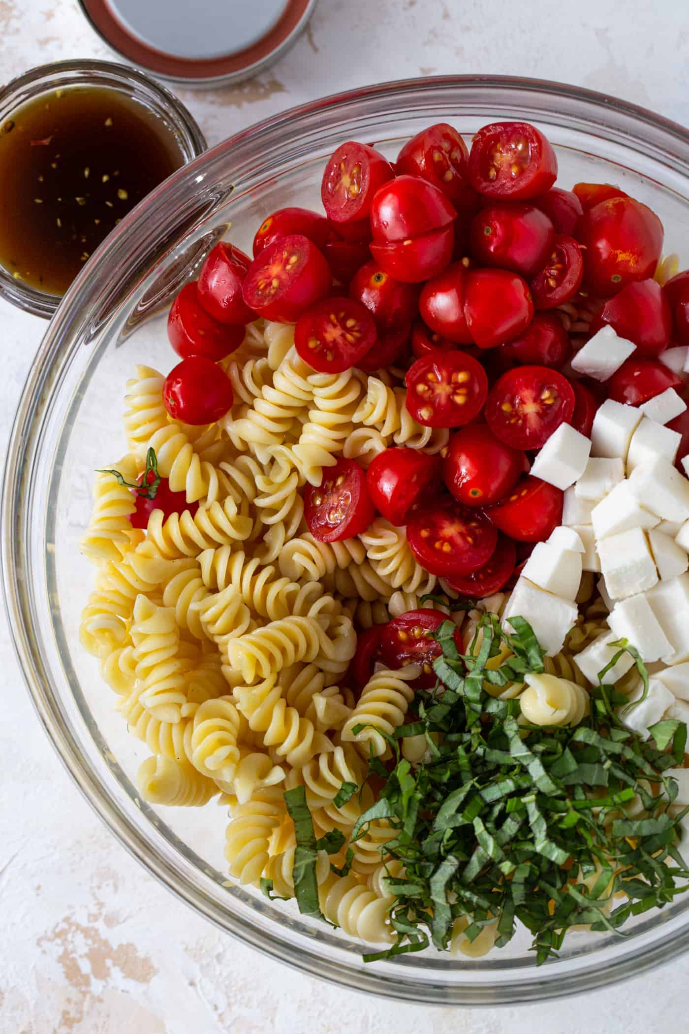 Glass mixing bowl filled with rotini pasta, cherry tomatoes, fresh basil and diced mozzarella.