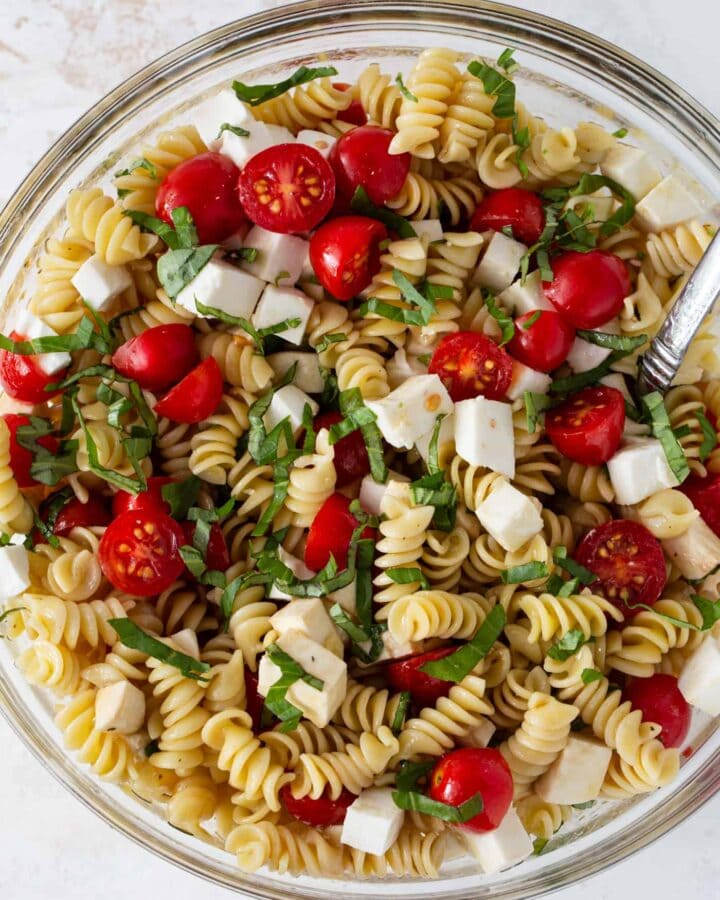 Glass mixing bowl filled with rotini pasta, fresh mozzarella, cherry tomatoes and fresh basil.