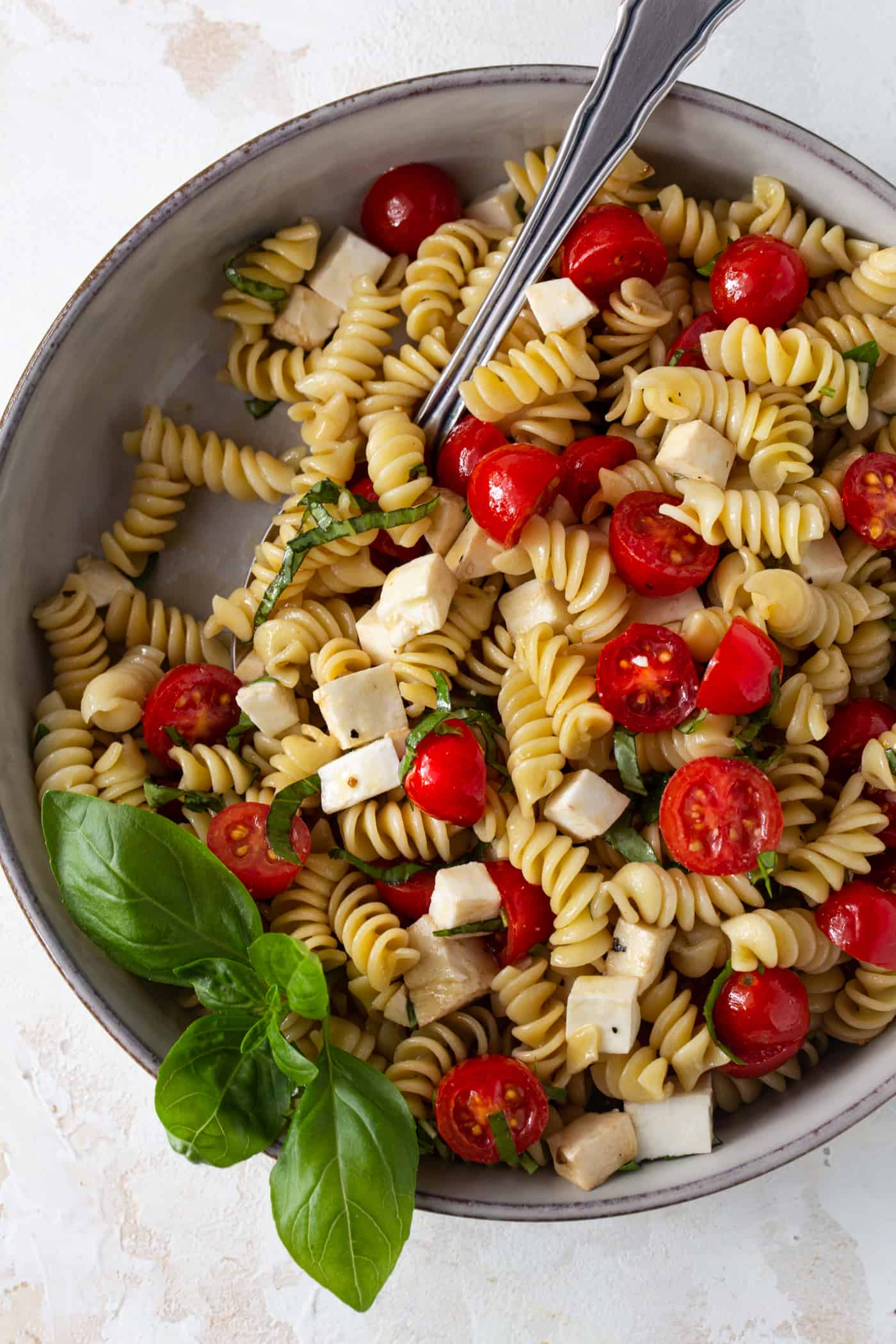 Top down image of caprese pasta salad in a gray bowl garnished with fresh basil leaves.