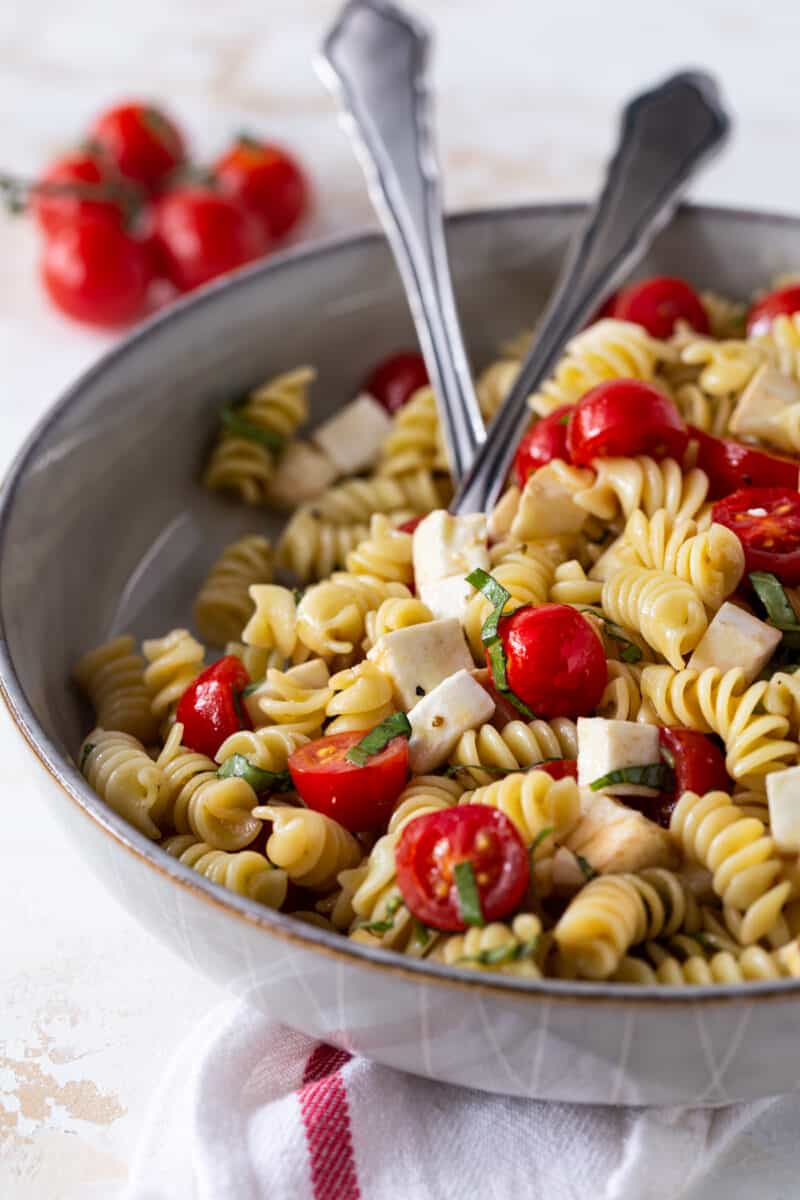 3/4 angle image of Caprese Pasta Salad in a gray bowl with a spoon for serving.