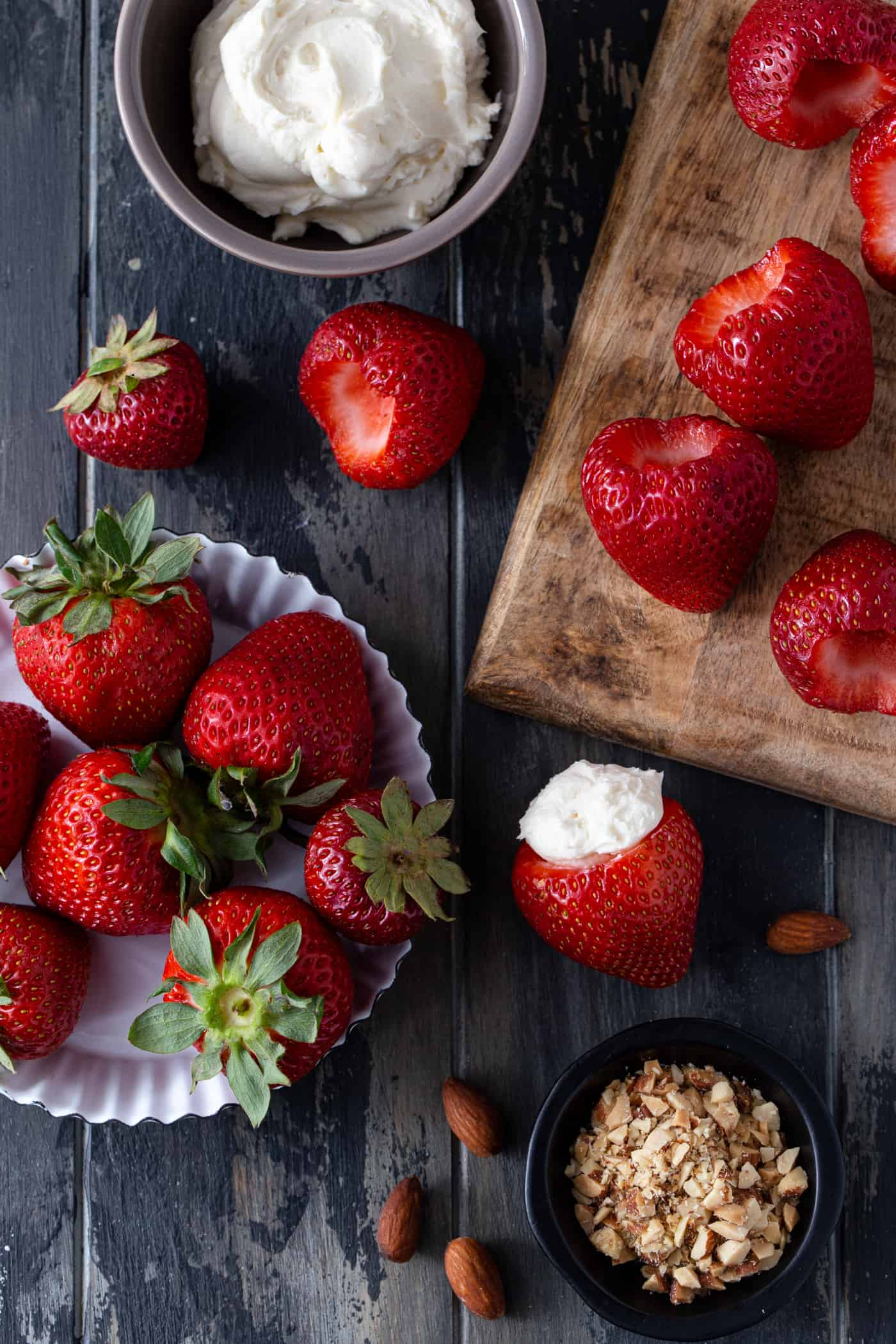 Strawberries on a wood cutting board with a bowl of cheesecake filling and a bowl of crushed almonds.