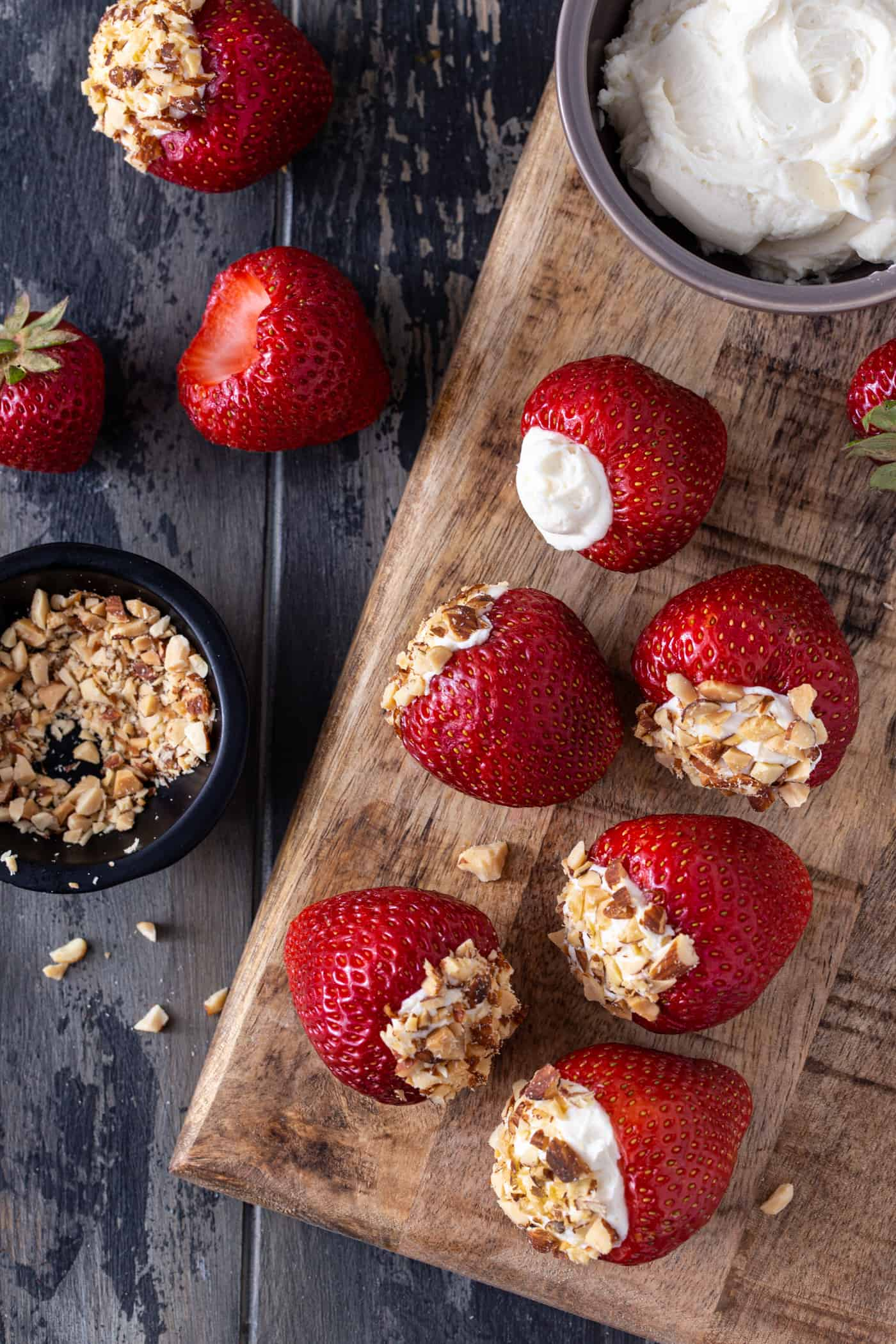 Strawberries on a wooden board stuffed with cheesecake filling and topped with crushed almonds