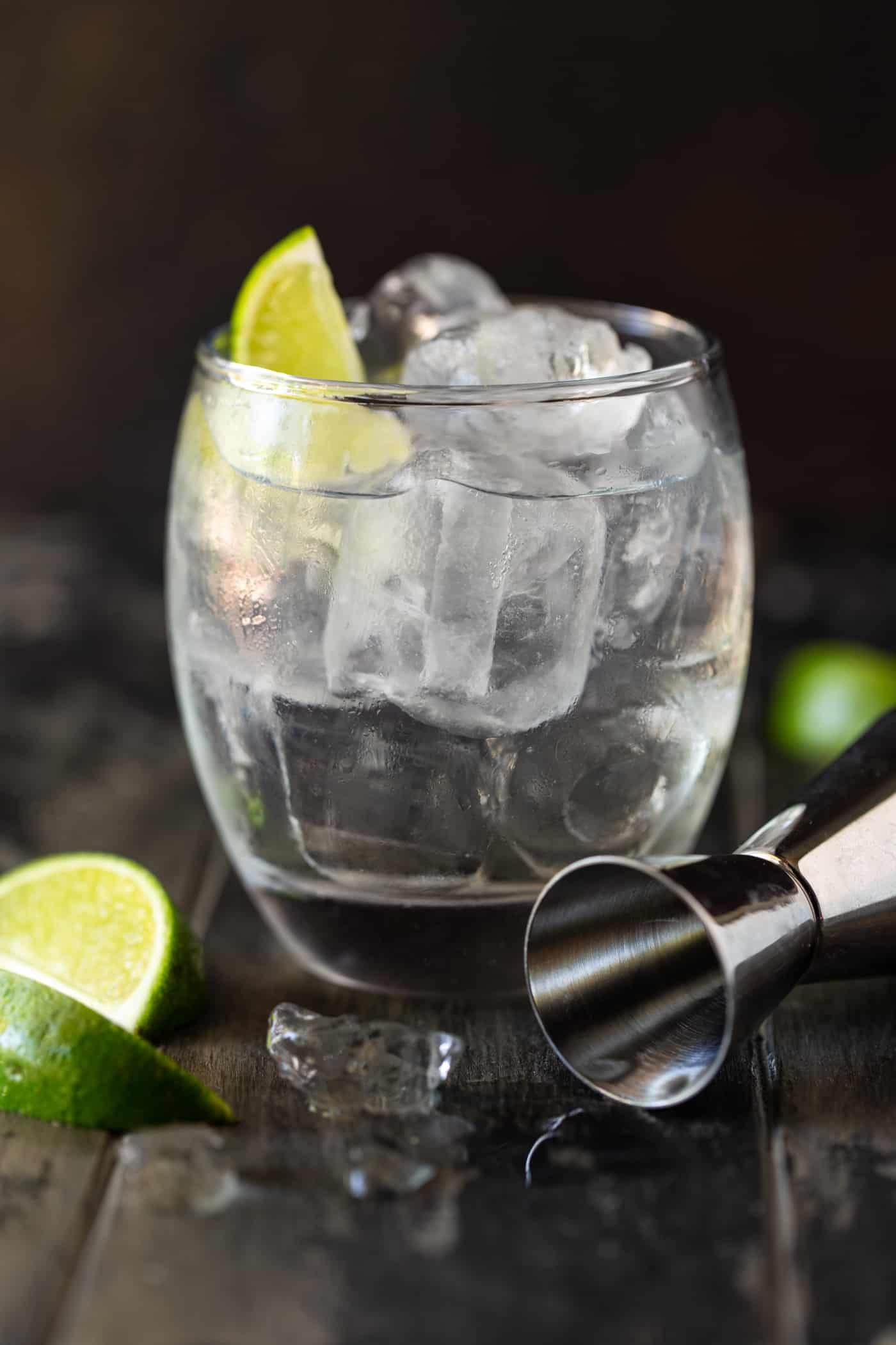Lowball glass filled with ice, gin, tonic water, elderflower liqueur and a lime wedge.