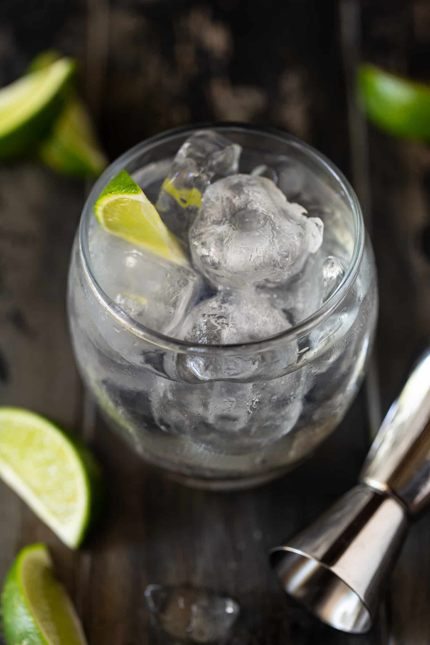 Top down view of a lowball glass filled with ice, gin, elderflower liqueur and tonic water. Garnished with fresh lime wedges.