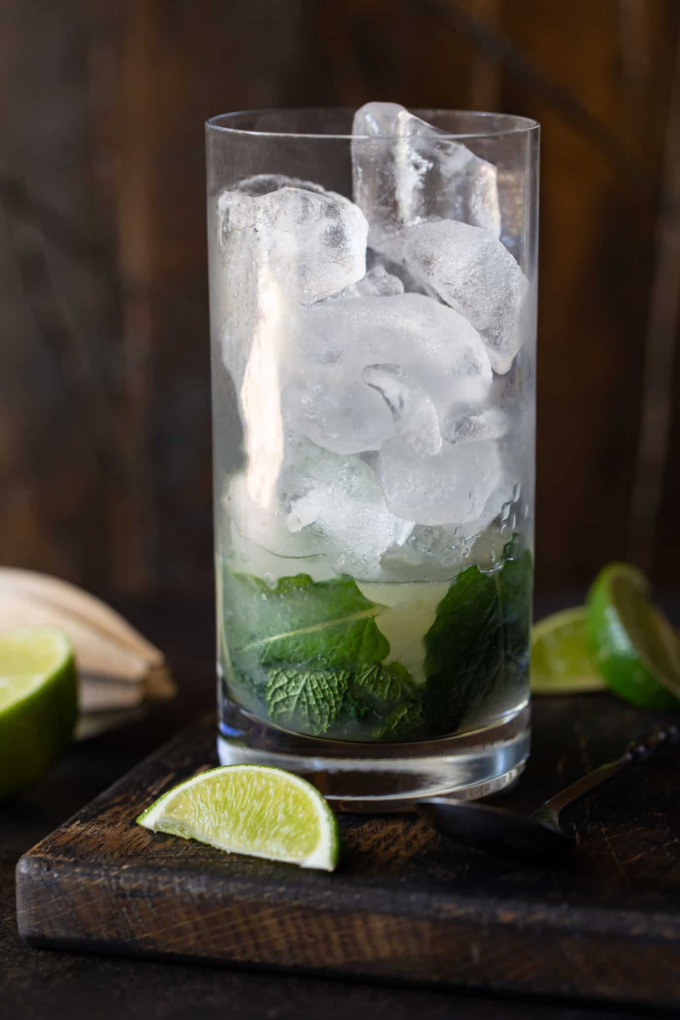 High ball glass with mint, sugar and lime muddled on bottom and filled with ice.