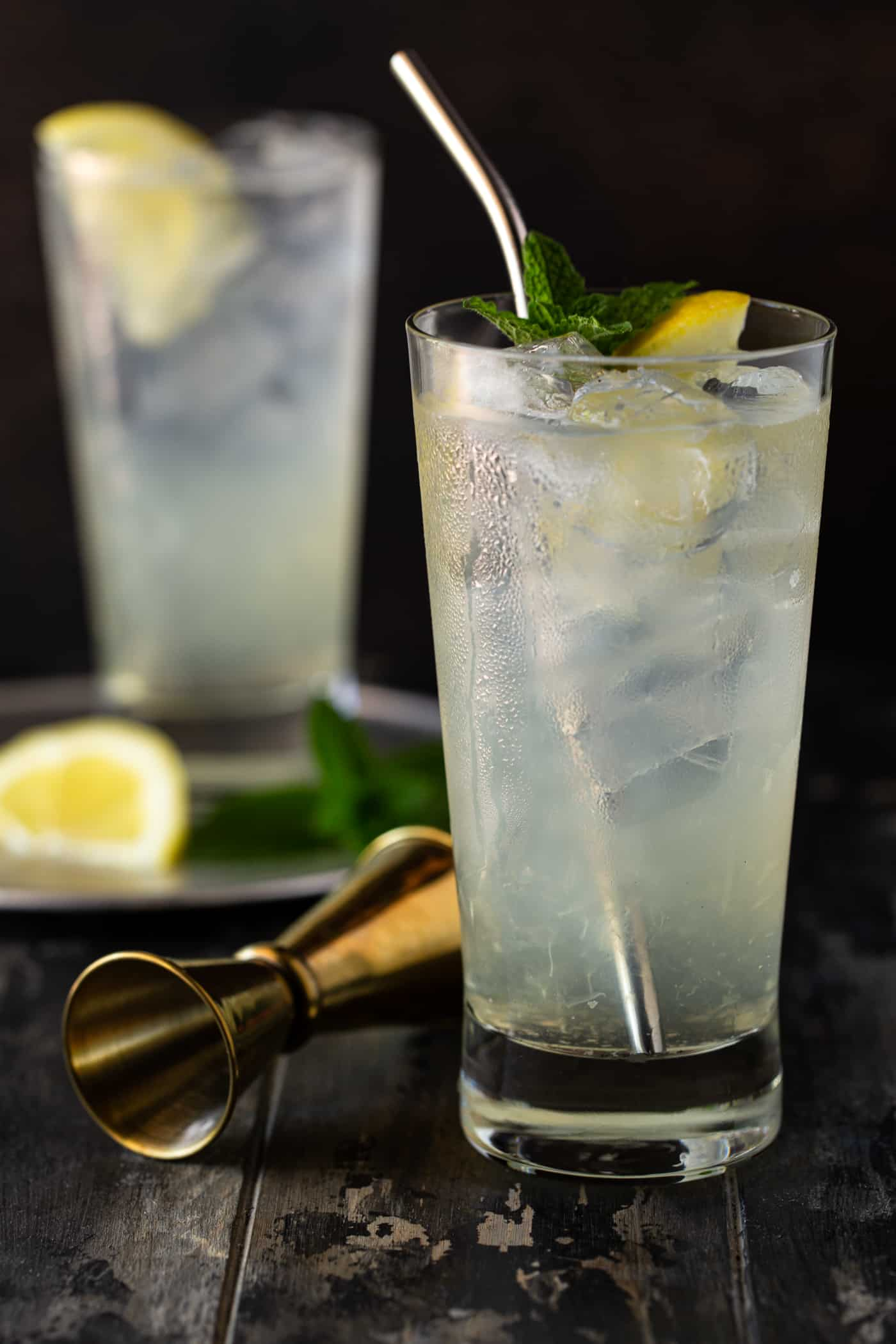 2 highball glasses filled with lemonade and fresh lemon wedges, mint leave and a gold shot glass on a dark background.