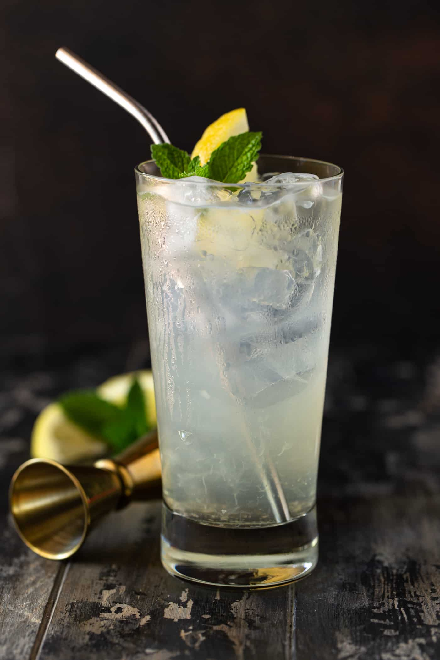 Single high ball filled with ice. lemonade and garnished with mint leaves and lemon wedges.
