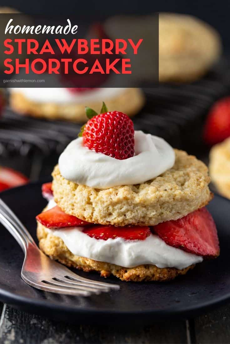 Shortcake recipe filled with fresh strawberries and homemade whipped cream on a dark background.