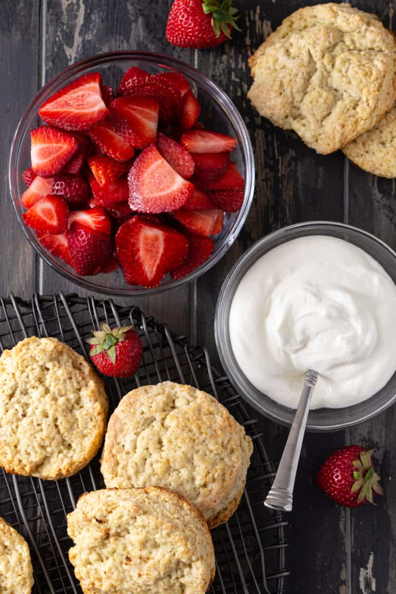 bowls of strawberries, whipped cream and shortcakes ready to be assembled for strawberry shortcake.