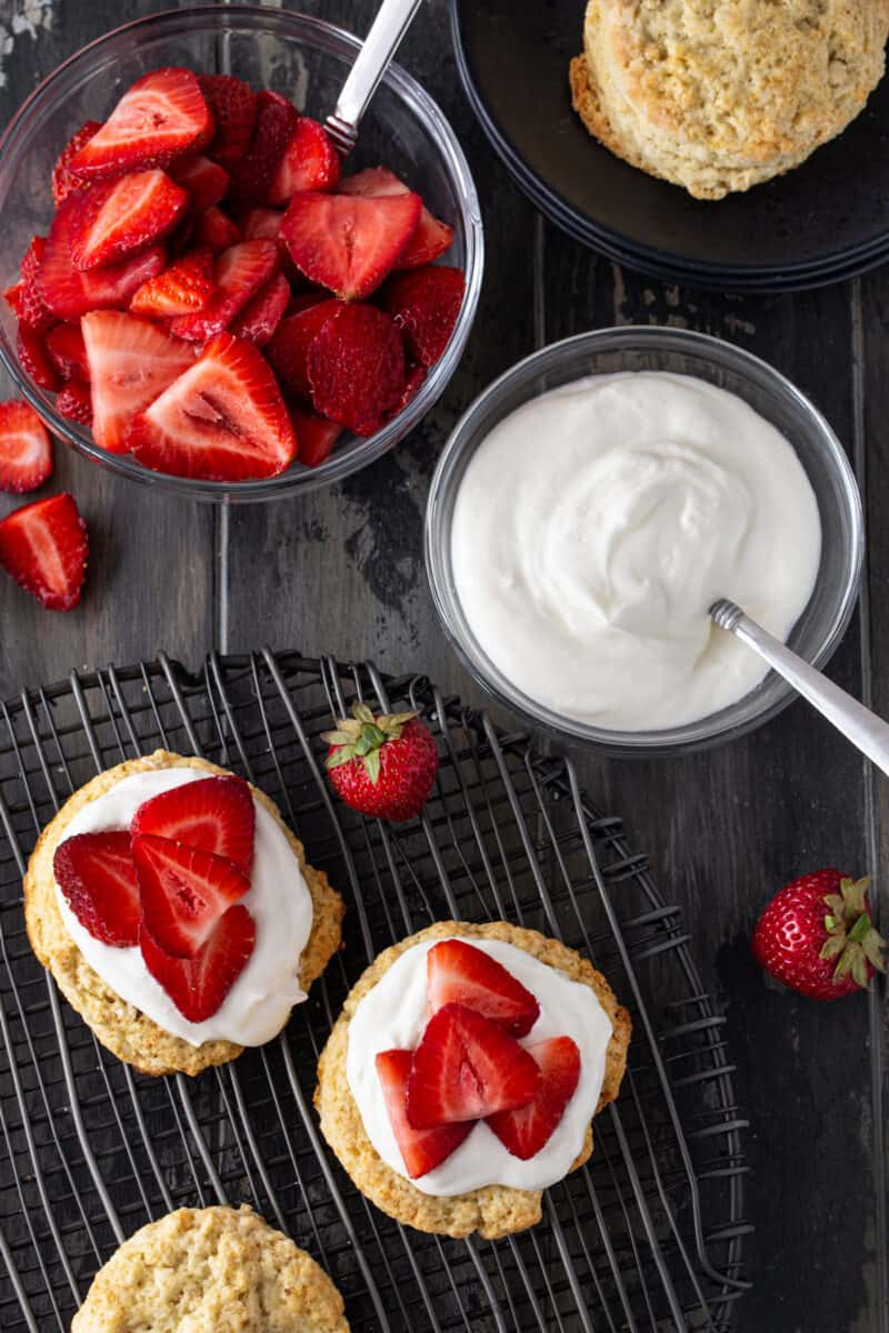 Strawberry shortcake recipe on a cooling rack with fresh strawberries for garnish.