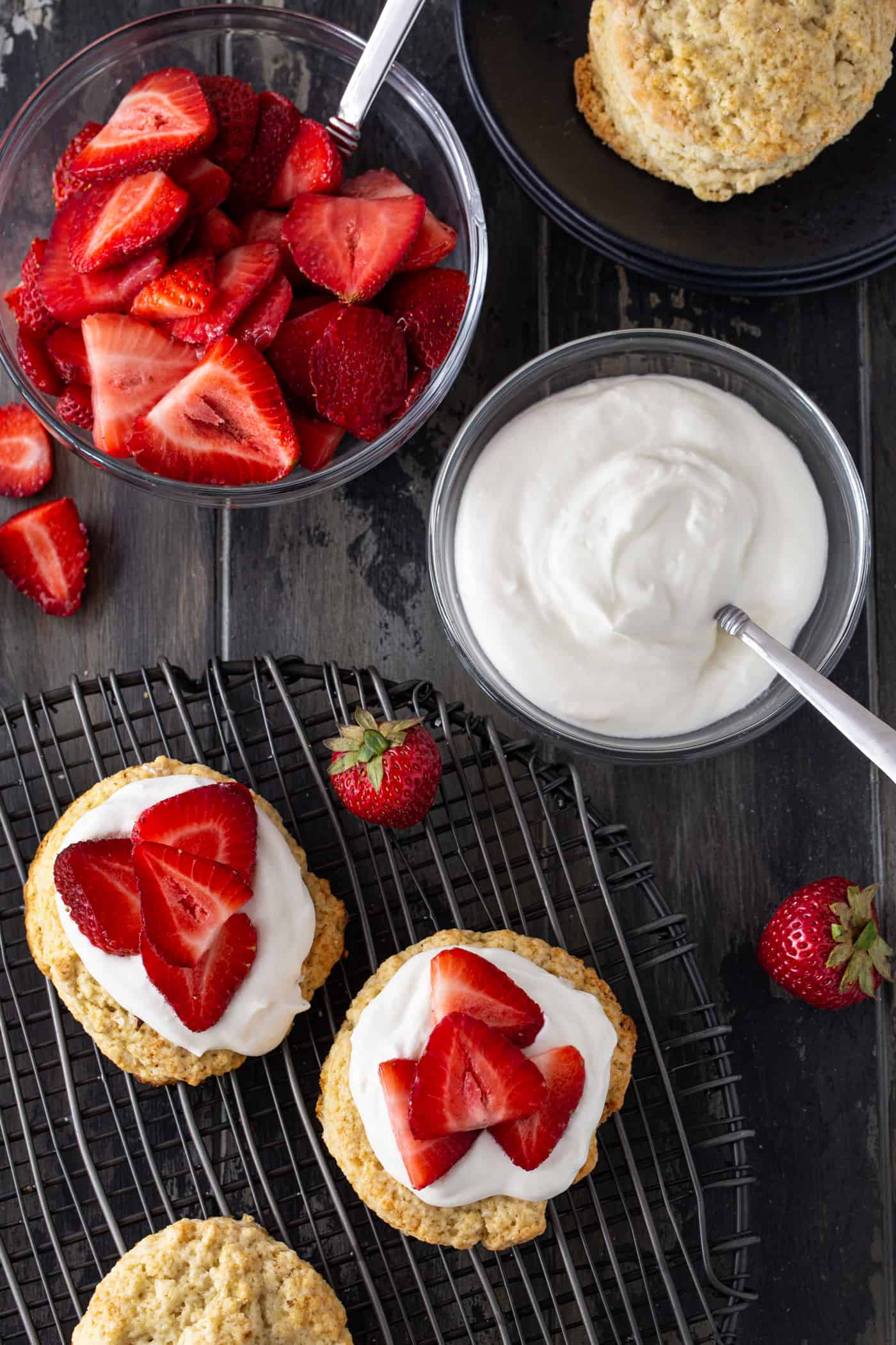 Strawberries, whipped cream and biscuits topped with fruit.