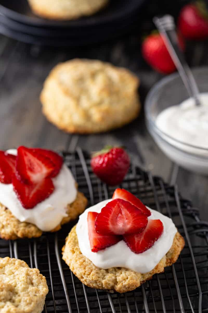 Strawberry shortcakes topped with whipped cream and fresh strawberries with a bowl of whipped cream and a biscuit in the background.