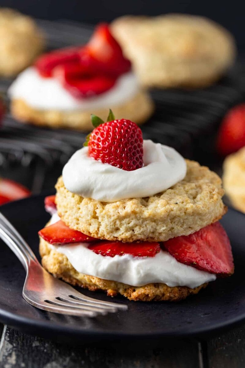 Strawberry short cake on a dark plate layered with sliced strawberries and whipped cream.