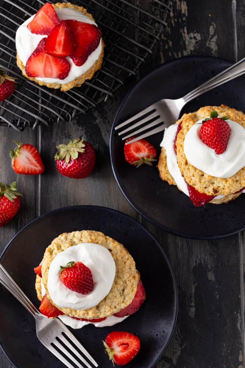fully assembles strawberry shortcake with fresh strawberries and homemade whipped cream on black plates with forks and fresh berries for garnish.