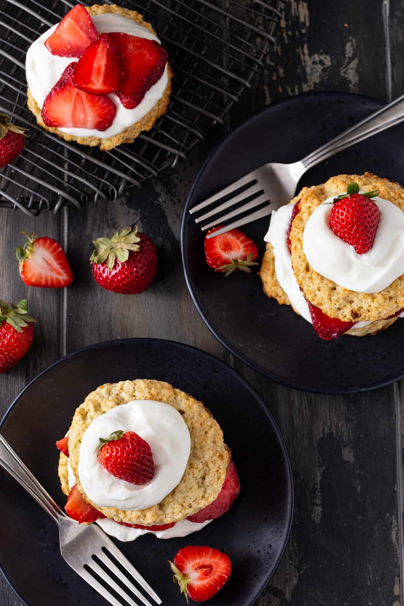Strawberry shortcakes on black plates with forks and extra strawberries as garnish.