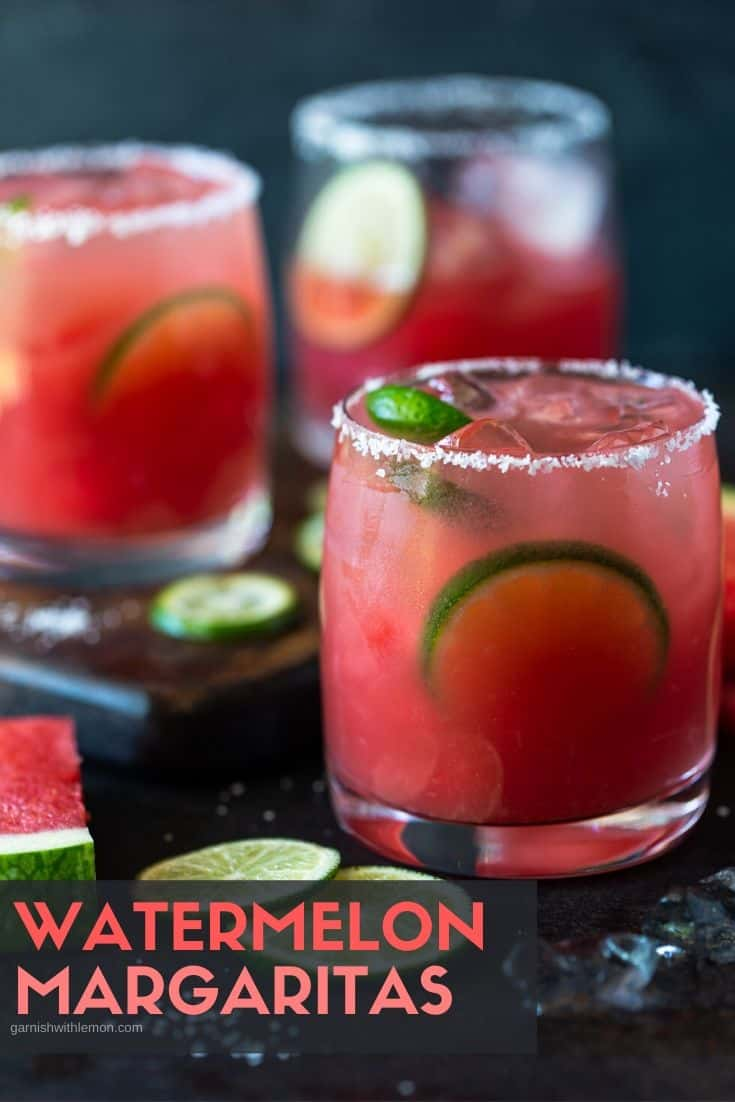 Lowball glasses with salted rims filled with fresh watermelon margaritas on the rocks and garnished with lime wheels and watermelon chunks.