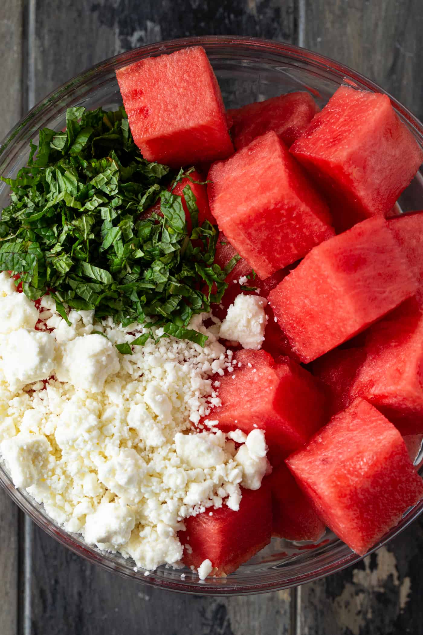 Fresh watermelon cubes, crumbled feta cheese and chopped mint leaves in a glass bowl.