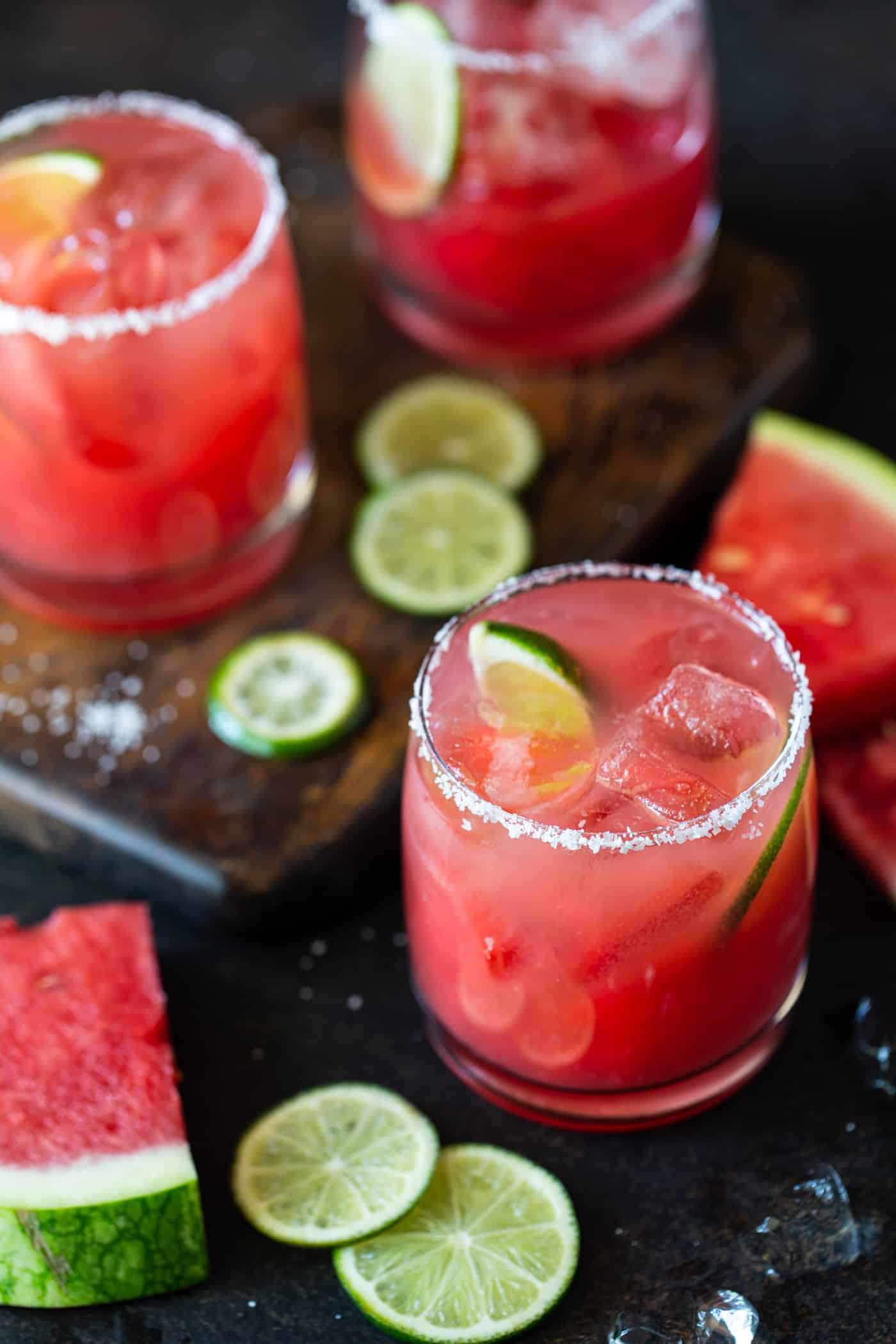 Lowball glasses with salted rims and filled with fresh watermelon margaritas on the rocks. Garnished with lime wheels and fresh watermelon chunks.
