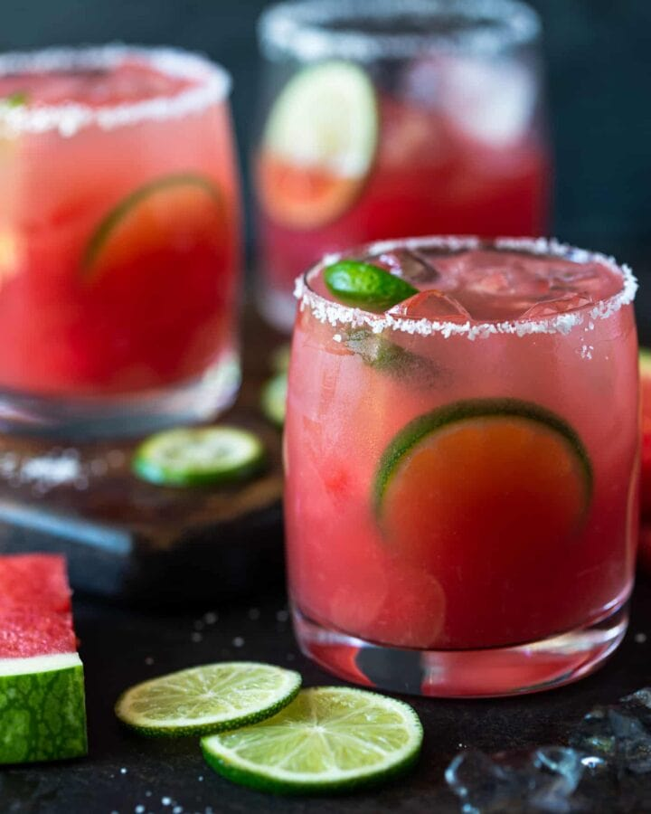 Lowball glasses rimmed with salt and filled with watermelon margaritas. Garnished with lime wheels and watermelon chunks.
