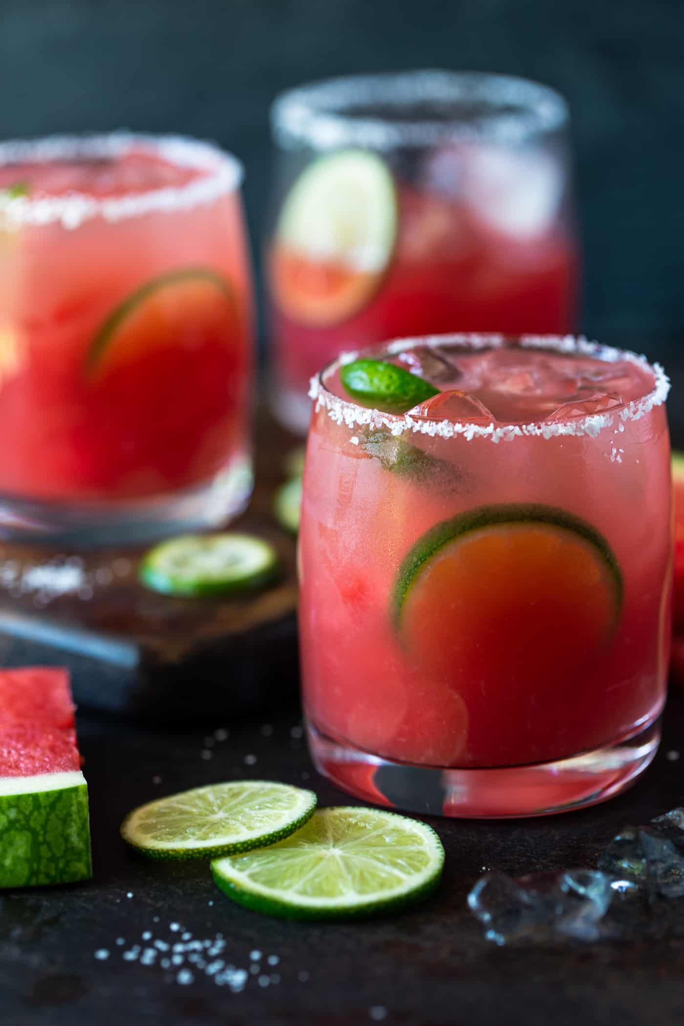 Lowball glasses rimmed with salt and filled with margaritas. Garnished with lime wheels and watermelon chunks.