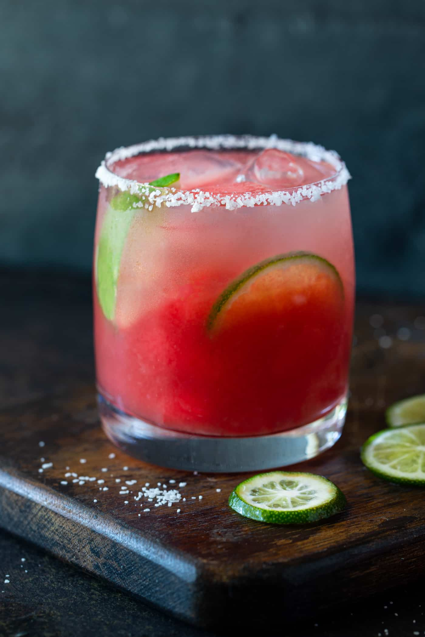 A watermelon margarita served in a lowball glass with salted rim. Garnished with fresh lime wheels and watermelon.