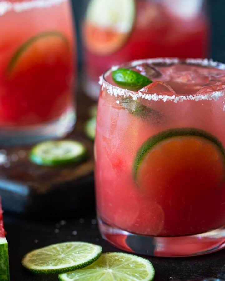 Watermelon margarita in an ice filled glass rimmed with salt and garnished with lime wedges.