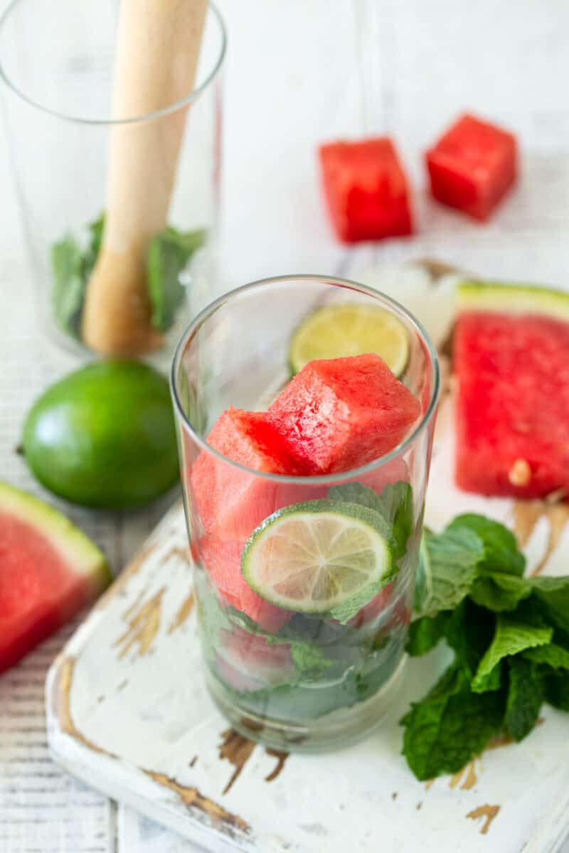 Highball glass filled with watermelon cubes, mint leaves, lime juice and sugar to make a watermelon mojito.
